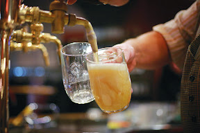 SABMiller: Photography of beer culture in the Czech Republic. A trained barman perfectly pours two draught jugs of Pilsner Urquell in a Prague pub.