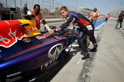 Себастьян Феттель катит свой Red Bull по пит-лейну на предсезонных тестах в Бахрейне 1 марта 2014