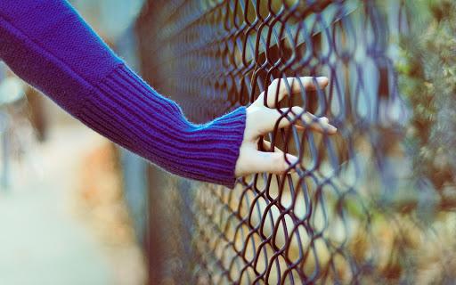 Girl's Hand on Fence