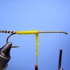 1. Ogonek wykonuję z pasemek prążkowanych piór cyranki, tułów nawijam z jasnożółtego dubbingu.