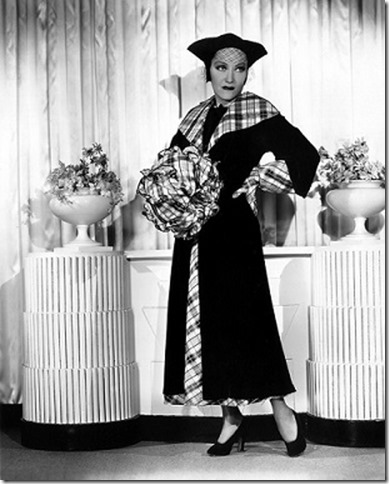 1934: American actress Gloria Swanson (1899 - 1983) models an ensemble designed by Rene Hubert of Fox Studios and worn by her in the film 'Music in the Air'. The outfit comprises a black velvet coat over a black and white taffeta gown with matching gloves and a handbag muff. (Photo by Otto Dyar)