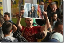 Un migrante con la foto di Angela Merkel