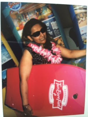 Me holding a boogie board and wearing a lai - Hawaiian style