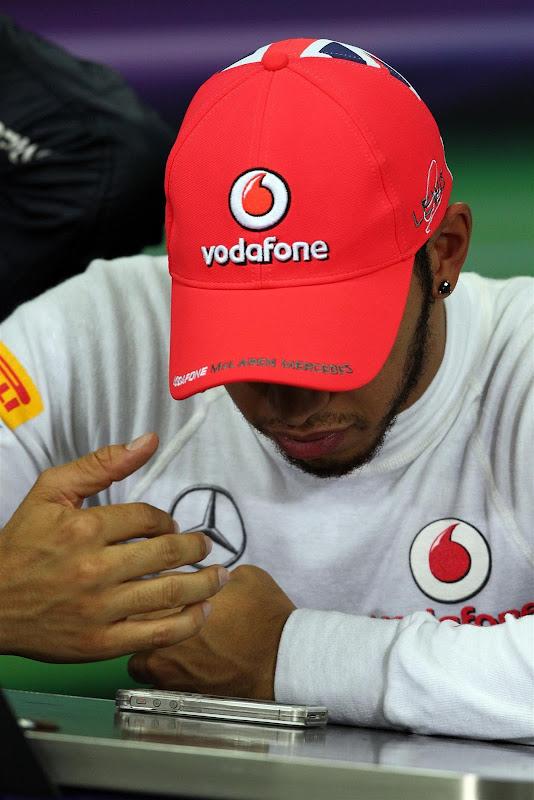 Льюис Хэмилтон смотрит в телефон на пресс-конференции в субботу на Гран-при Кореи 2012