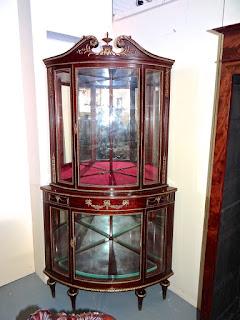 Угловая витрина полукруглой формы с двумя дверками. 19-й век. Красное дерево, позолоченная бронза. 100/60/240 см. 10500 евро.