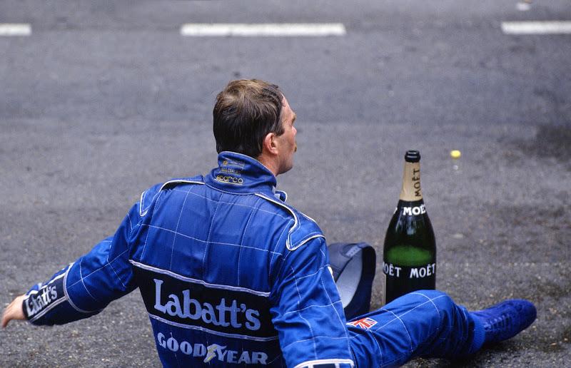 Найджел Мэнселл сидит на асфальте с бутылкой шампанского после финиша на 2-ом месте на Гран-при Монако 1992