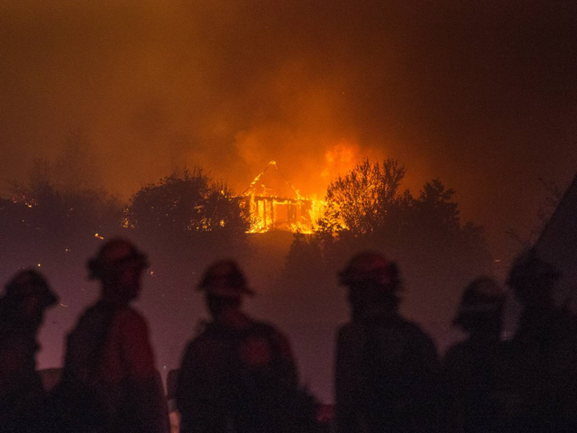 In this Sunday, 28 June 2015 photo provided by The Wenatchee World, Forest Service fire fighters from Leavenworth watch as a house burns in northern Wenatchee, Washington. A wildfire fueled by high temperatures and strong winds roared into a central Washington neighborhood, destroying properties and forcing residents of several hundred homes to flee, authorities said Monday. Photo: Don Seabrook / The Wenatchee World via AP