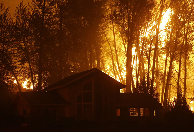 A wildfire burns behind a home on Twisp River Road, 20 August 2015. Photo: Ted S. Warren / AP