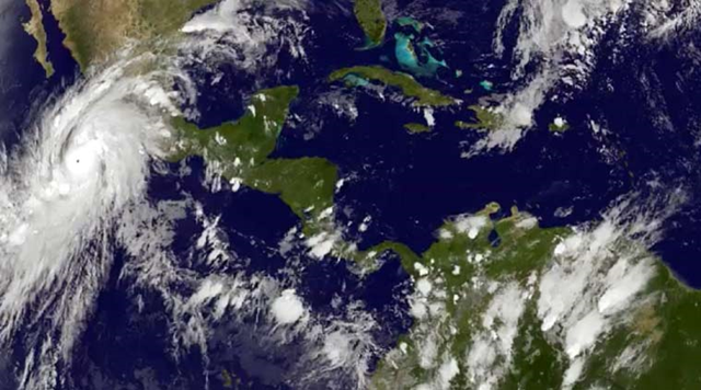 This satellite image taken at 8:45 p.m. EDT on Thursday, 22 October 2015, and released by the National Oceanic and Atmospheric Administration shows Hurricane Patricia, left, moving over Mexico's central Pacific Coast. Photo: NOAA