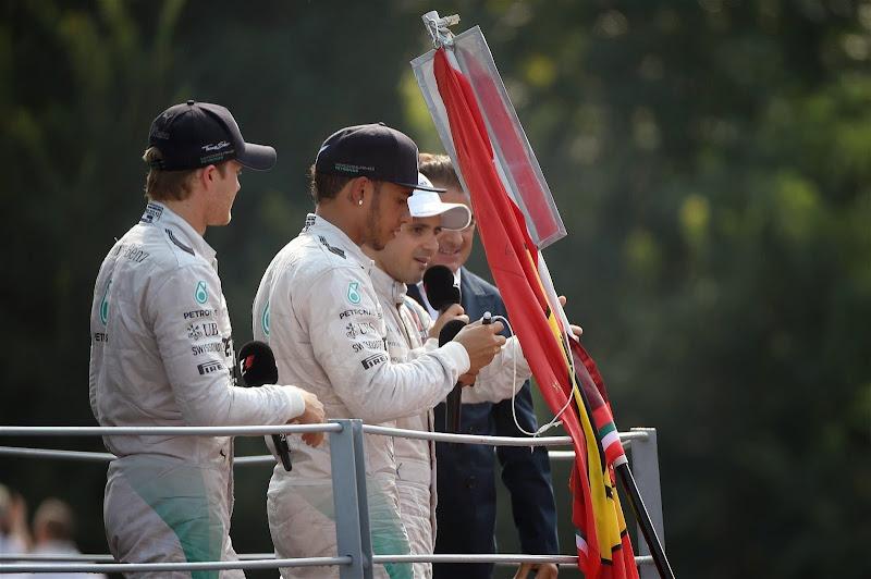 Льюис Хэмилтон ставит автограф на флаге болельщика на подиуме Монцы на Гран-при Италии 2014