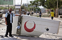 A Palestinian medic shows the cover of a Red Crescent ambulance destroyed by an Israeli strike, as he and residents visit the area during a 12-hour cease-fire in Beit Hanoun, northern Gaza Strip, Saturday, July 26, 2014. Thousands of Gaza residents who had fled Israel-Hamas fighting streamed back to devastated border areas during a lull Saturday to find large-scale destruction: scores of homes were pulverized, wreckage blocked roads and power cables dangled in the streets. (AP Photo/Lefteris Pitarakis)