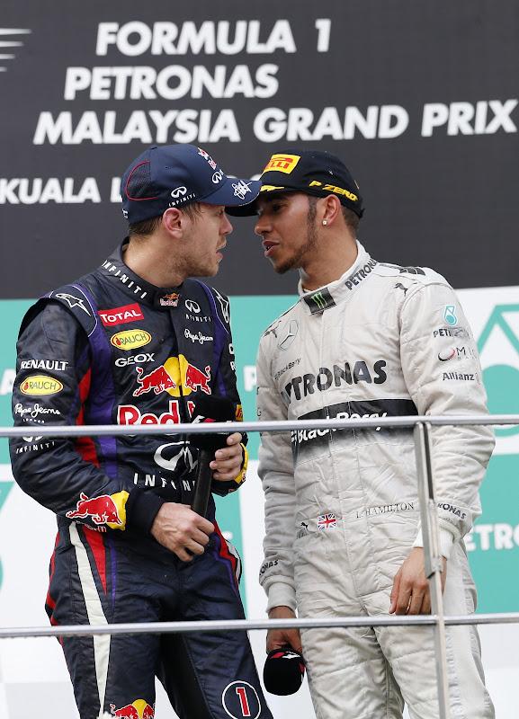 Себастьян Феттель и Льюис Хэмилтон обсуждают что-то на подиуме Гран-при Малайзии 2013