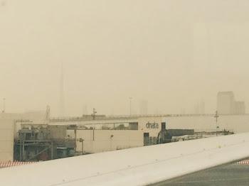 Et bilde fra en tåkete flyplass med Dubai i bakgrunnen.