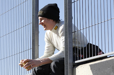 улыбающийся Кими Райкконен сидит на заборе на тестах в Валенсии 23 января 2012