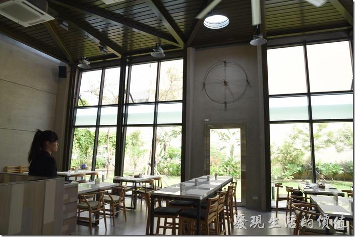 台南森兜風餐廳內的景象,大片的落地窗,旁邊就是綠地及樹木,牆壁上僅用鐵絲繞出一個時鐘的樣子。