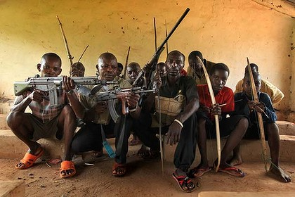 Protecting their families ... the Arrow Boys Samuel Manese 2nd from left and Deputy Chief Acquila Daniel 4th from right at rear, use an array of weapons against the insurgents. Photo: Kate Geraghty.  Kate Geraghty travelled to Sudan courtesy of Doctors Without Borders. Posted to CONGO WATCH  http://congowatch.blogspot.com/2010/11/meet-arrow-boys-south-sudanese-tribal.html 26 Nov 2010