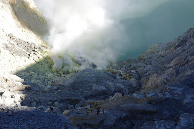 The view down into Ijen crater from the rim. Sulfur mining operations take place at the bottom, near the gas clouds.