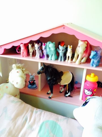 Maegan's pony collection on her dollhouse bed