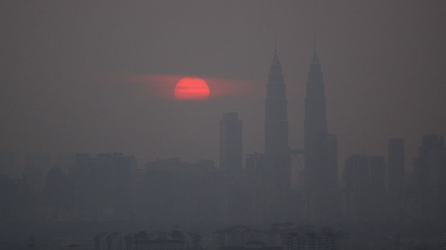 Kuala Lumpur, Maylasia swelters under peat-fire smog during late September of 2015. Ever since 1997, Indonesia has suffered severe seasonal wildfires. These fires are often set by corporate and individual farmers who use the fires to clear land. However, increased heat and drought caused by an increasingly vicious human-forced warming of the globe are creating a climate in which these fires, once set, tend to rage out of control. Photo: ALERT