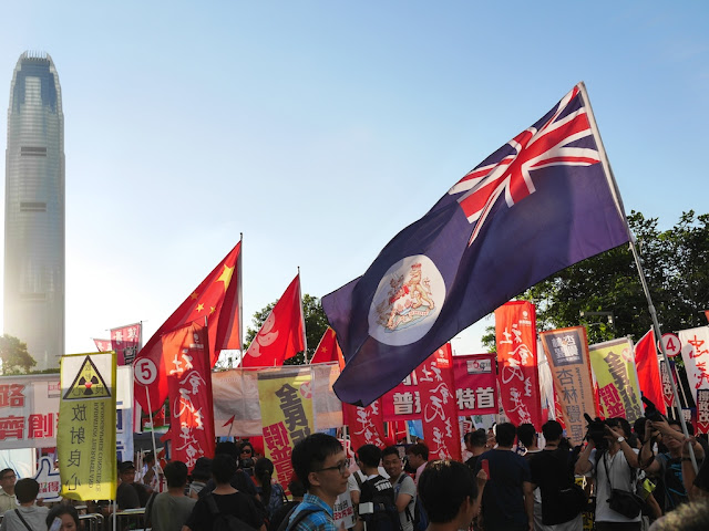 old flag for the British Colony of Hong Kong being waved along with the current Hong Kong flag and PRC flag in the background