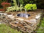 Pojemnik budowlany zakopany w ziemi i obudowany murkiem z łupka.