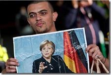 Un migrante mostra la foto di Angela Merkel