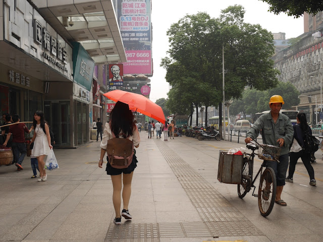 woman holding an umbrella walking by a construction worker in Changsha