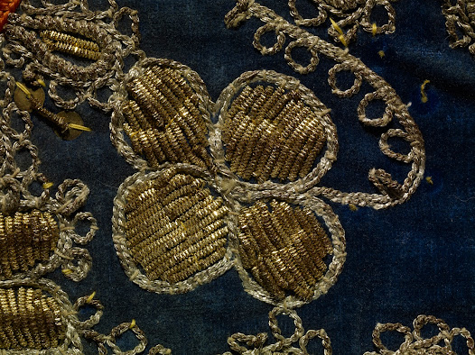 This waistcoat is made of cotton velvet cloth decorated back and front with couched embroidery in gold- and silver coloured metal-wrapped thread, metal sequins and tiny red plastic beads. The printed cotton lining dates from the 1920s or 1930s. The flowers and leaves on the front flaps are done in purl work (see Albanian hair ornament).