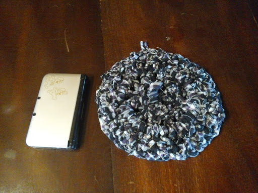 large crocheted trivet in the same pattern as the above yarn (a blue and purple plaid), slightly larger in diameter than a Nintendo DS XL.