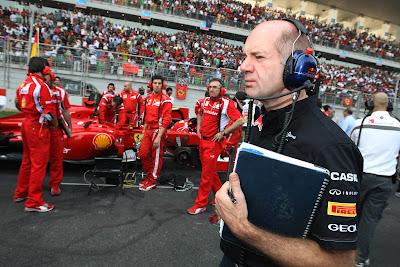 Эдриан Ньюи проходит мимо болида Ferrari на стартовой решетке Гран-при Индии 2011