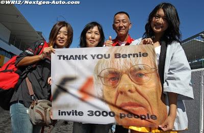 болельщики на пит-лейне с плакатом Берни Экклстоуна на Гран-при Японии 2011