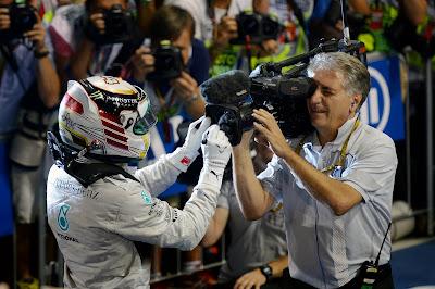 Льюис Хэмилтон ставит автограф на объективе телевизионной камеры на Гран-при Абу-Даби 2014