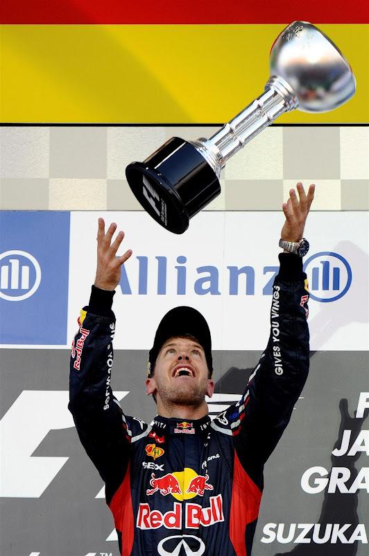 Себастьян Феттель кидает свой трофей в воздух на подиуме Сузуки на Гран-при Японии 2012