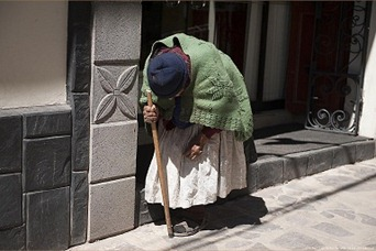 Hunchbacked old woman in Puno, Peru.