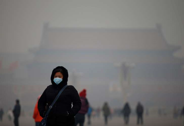 A woman wearing a mask makes her way during a polluted day at Tiananmen Square in Beijing, 15 January 2015. Photo: Kim Kyung-Hoon / Reuters