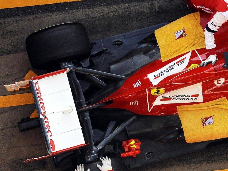 механики покрывают болид Ferrari полотенцами на предсезонных тестах в Барселоне 3 марта 2013