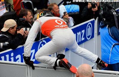 Льюис Хэмилтон перепрыгивает ограждение закрытого парка после победы на Гран-при Германии 2011 вид со спины