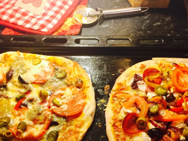 Homemade thin crust pizzas with meat and vegetables