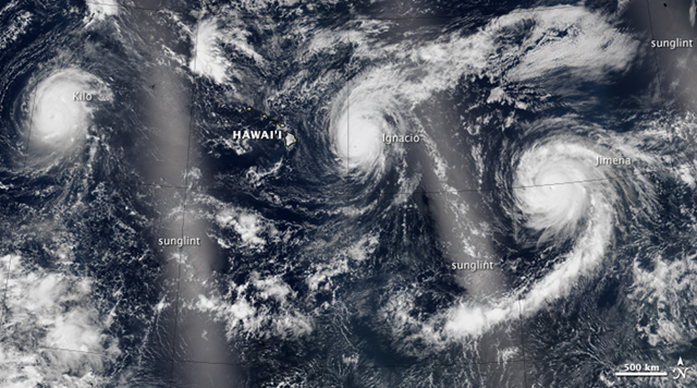 This image shows hurricanes Kilo, Ignacio, and Jimena (from west to east) on 30 August 2015. This natural-color image is also a mosaic, acquired with VIIRS between about 11 a.m. and 2 p.m. Hawaii Standard Time on August 30 (21:00 and 00:00 Universal Time on August 30-31). The bright areas are due the mirror-like reflection of sunglint. Photo: Jesse Allen