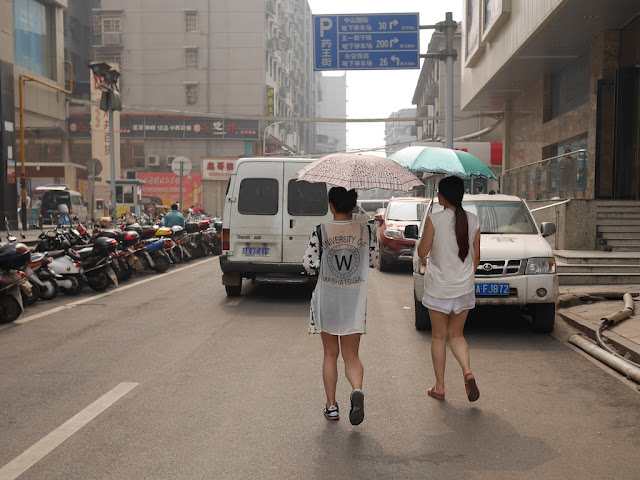 two young women holding sun umbrellas walking down a street in Changsha