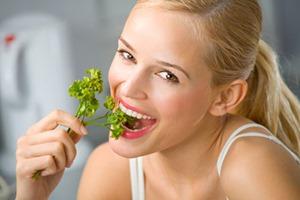 Девушка ест салатный листик