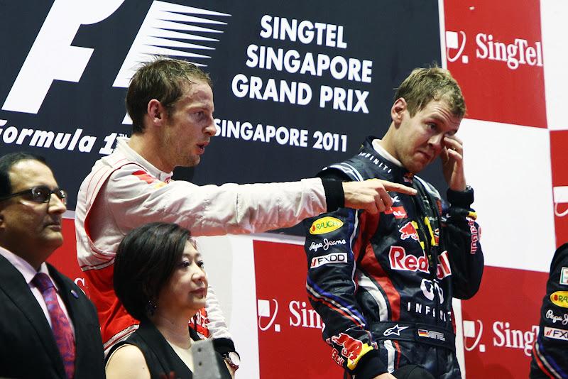 Дженсон Баттон указывает куда-то пальцем и Себастьян Феттель на подиуме Гран-при Сингапура 2011
