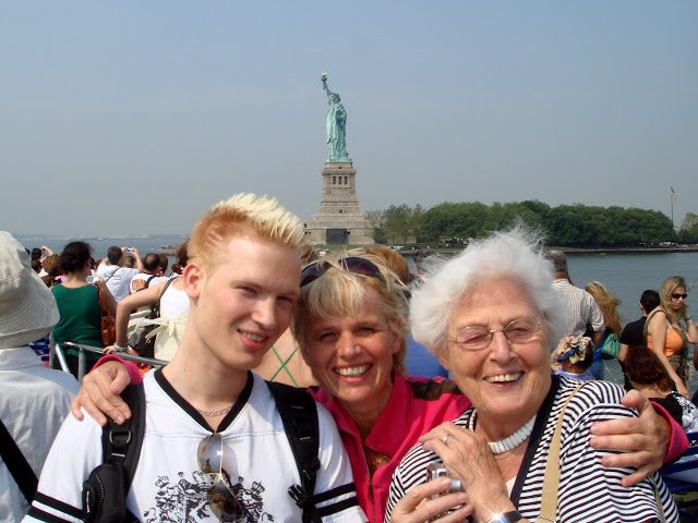three generations in front of the statue of liberty in New York City, New York, United States
