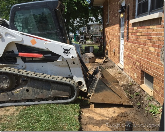 Taking out an old concrete sidewalk with a bobcat