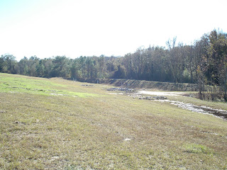 A typical closed landfill requires continuous maintenance. Here a sediment pond has been cleared but more work remains to improve drainage as indicated by the ponded water on the right.