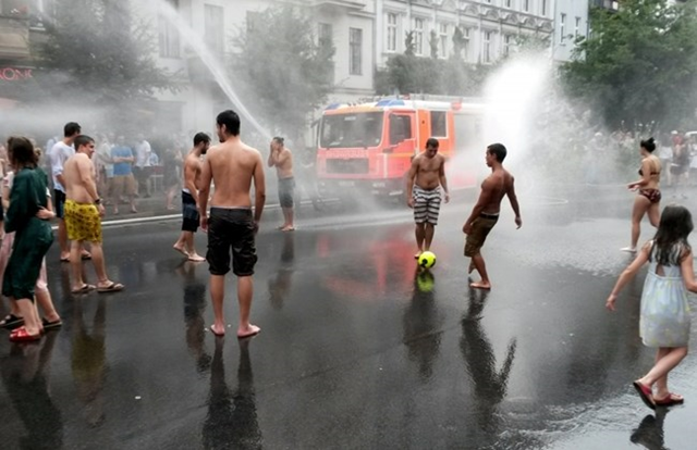 People shower in the street to cool down as fire brigades use their equipment to refresh residents and visitors during a hot summer day on 5 July 2015 in Berlin's Prenzlauer Berg district. Temperatures in the German capital reached around 37 degrees Celsius. Photo: FRANK ZELLER / AFP PHOTO