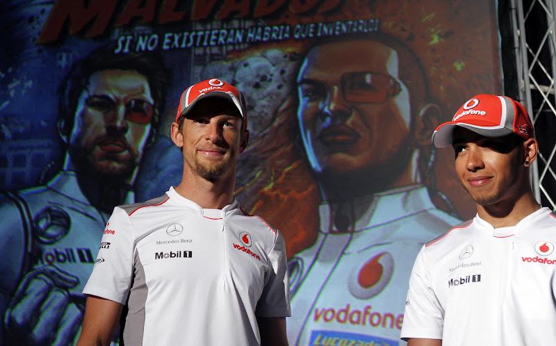 Дженсон Баттон и Льюис Хэмилтон на презентации комикса на фоне своих персонажей перед Гран-при Испании 2012