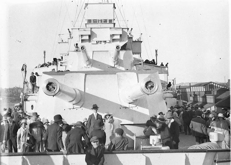 El HMAS AUSTRALIA en el puerto de Sydney, atracado en Woolloomooloo. Se aprecia el puente mas bajo en comparación con el CANARIAS. Foto de la State Library of New South Wales.jpg