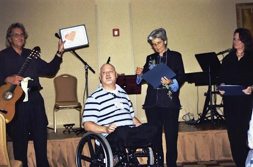 Andre presents an award of recognition to Janalea Hoffman, Antonio Esteban, & Elaine Cormany.