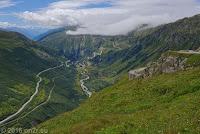 Furkapass, Westrampe. Blick ins Rhonetal. Links die Furkastraße, die im Rhonetal in Richtung Mont Blanc nach Frankreich führt. Unten am Talausgang das Örchen Gletsch, wo die Grimselstraße abzweigt und sich hinauf zum Grimselpaß windet. In der Bildmitte schlängelt sich die Rhone, die rechterhand am Rhonegletscher ihren Ursprung hat. Nach über 800 km mündet sie in Südfrankreich in der Camargue ins Mittelmeer.